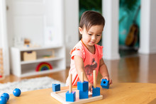 Toddler Girl Playing And Exploring With Montessori Lessons