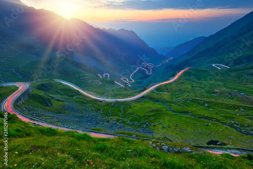 Photo Stands Black Traffic trails on Transfagarasan pass at sunset. Crossing Carpathian mountains in Romania, Transfagarasan is one of the most spectacular mountain roads in the world