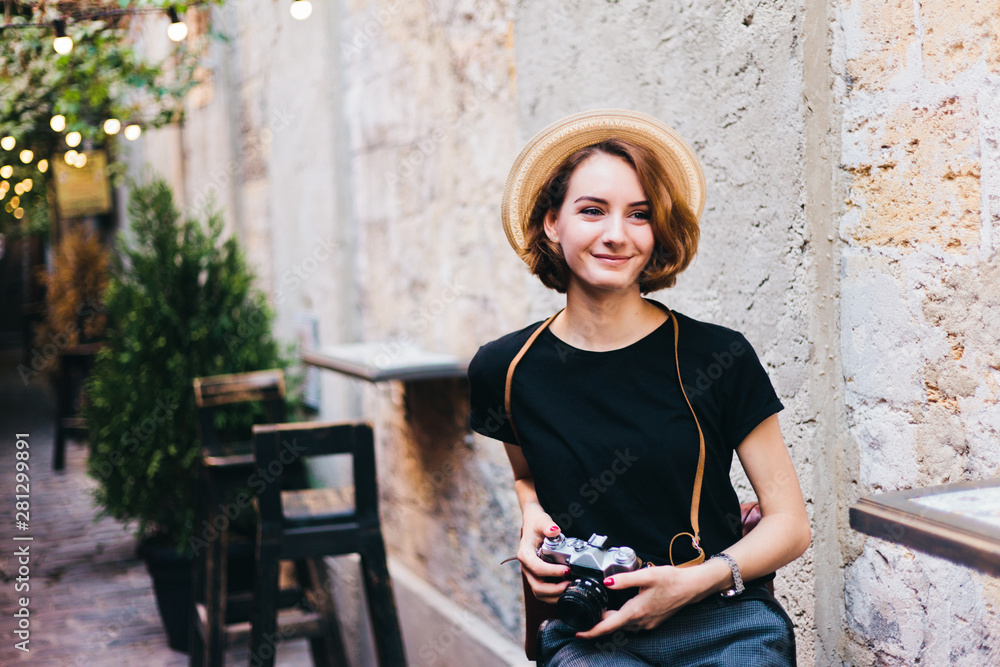 Fototapeta Young hipster with retro camera in hands sits on chair and smiles outdoors against the backdrop of garlands