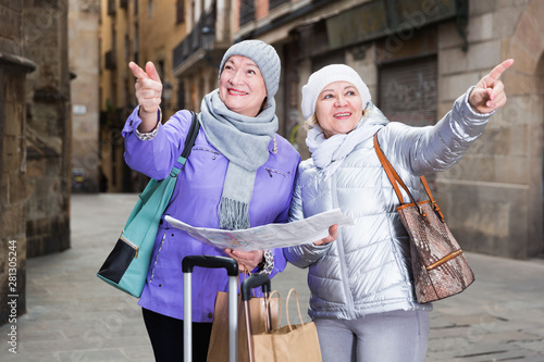 Photo  Senior females traveling with city map