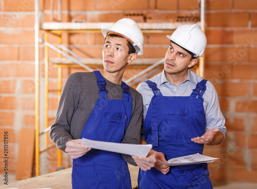 Builders reading plan of brick building