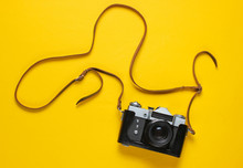 Vintage Retro Film Camera In Leather Cover With Strap On Yellow Background. Top View