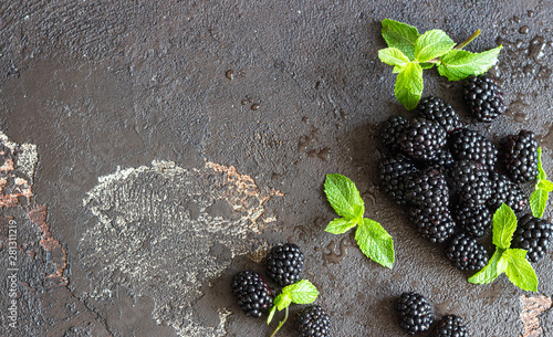 Poster Spa Ripe blackberries with mint leaves on a dark brown stone background. Selective focus, copy space.