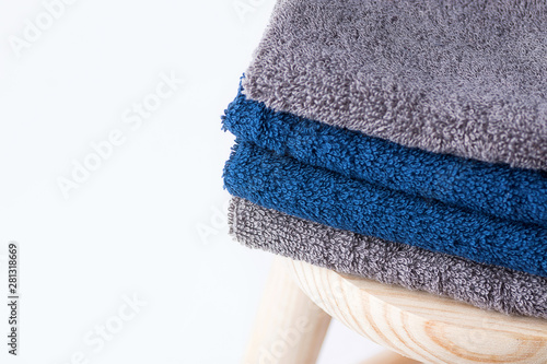Papel de parede Folded cotton terry towels washcloth on wooden chair on white background