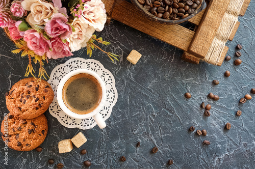 breakfast in vintage style. A cup of coffee with pieces of cane sugar, biscuits with chocolate and a vase with coffee beans. Top view