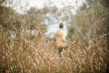 Boy Playing In High Grass