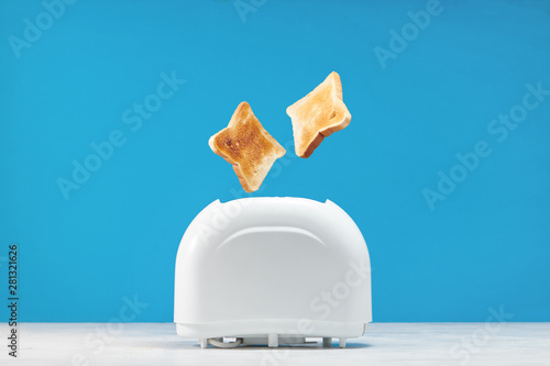 Fotomural  Roasted toast bread popping up of toaster with blue wall