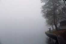 Woman Standing On River Bank In Foggy Autumn Morning