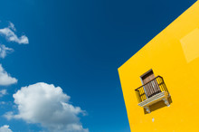 Yellow Wall And A Balcony Against The Blue Sky