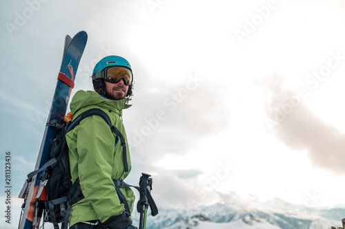 portrait of a skier on the top of a mountain