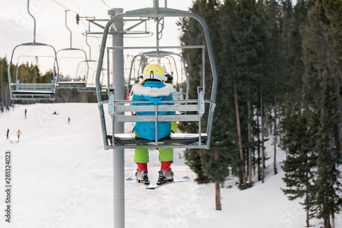 Pre-teenage girl on a chairlift viewed from behind