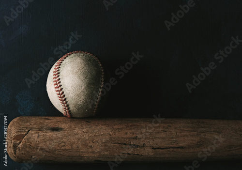 Obraz na plátne Baseball sport shows ball with bat on black background, moody and tough sports concept with copy space