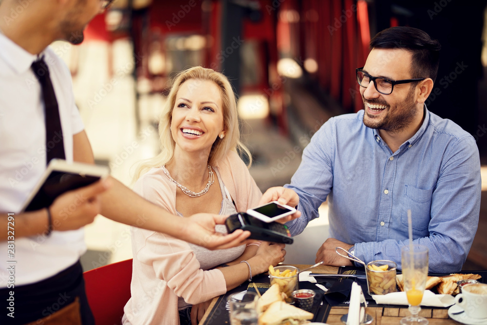 Fototapeta Happy couple paying a bill with smart phone on card machine in a restaurant.