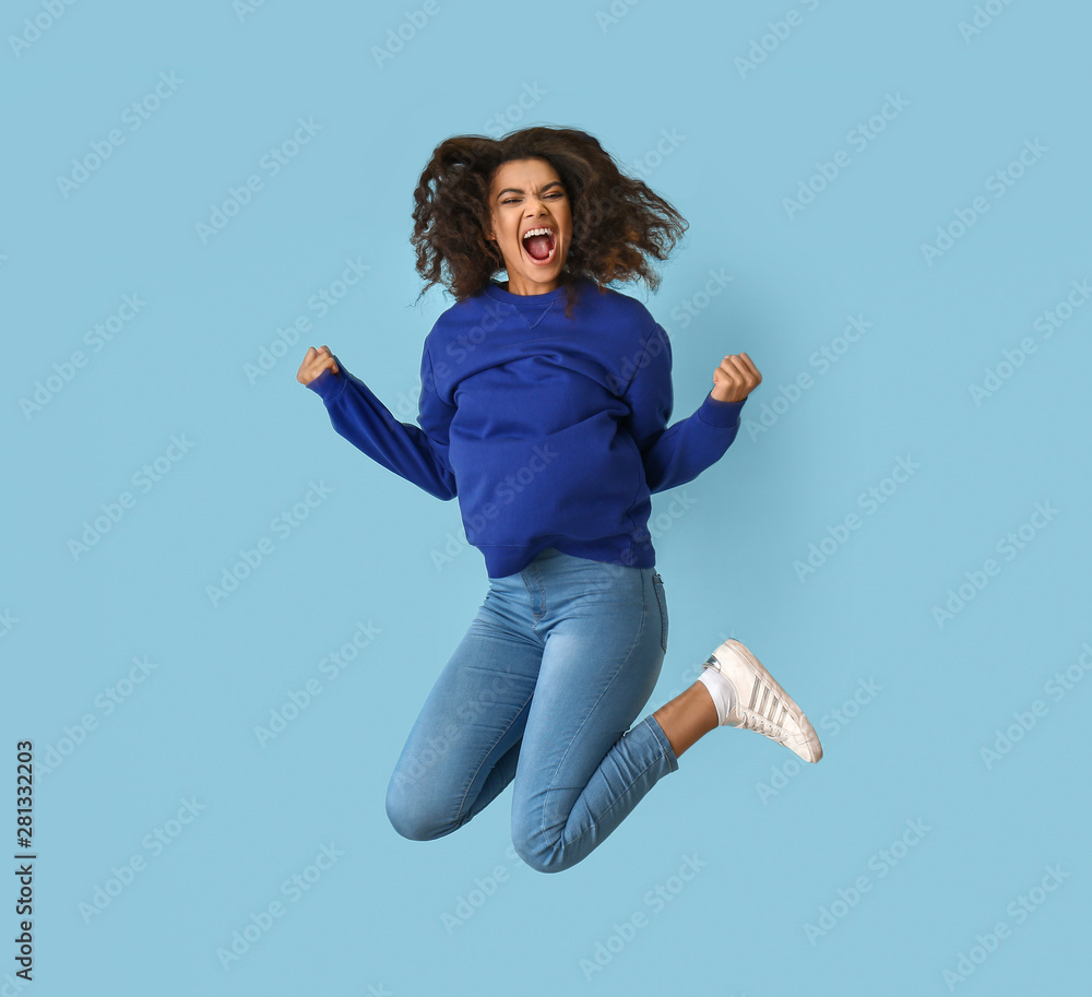 Fototapety, obrazy: Jumping African-American woman on color background