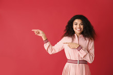 Portrait Of Happy African-American Woman Pointing At Something On Color Background