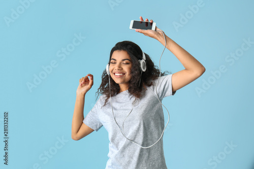Foto auf Leinwand Logo Portrait of happy African-American woman listening to music on color background