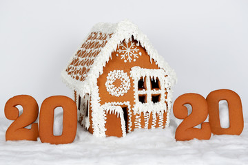 The hand-made eatable gingerbread house, 2020 inscription, snow decoration, on white background