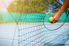 Selective Focus To Net With Blurry Tennis Ball In Hand And Racket In Court Under Sunlight. Tennis Game. Sport, Recreation Concept