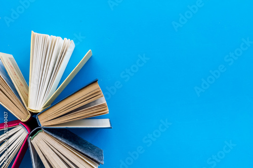 Books on library desk for reading and education on blue background top view mock Fototapeta