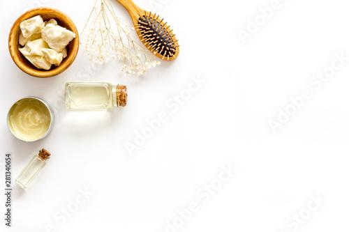 Fototapeta  Bottle with jojoba, argan or coconut oil, styling, comb for hair style on white