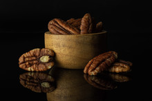 Lot Of Whole Fresh Brown Pecan Nut Half In A Wooden Bowl Isolated On Black Glass