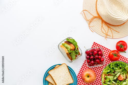 Fotografia picnic in summer with products, sandwich, salad, fruits and hat on white backgro