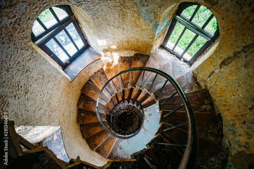 Fototapeta Old spiral staircase in abandoned mansion, upside view