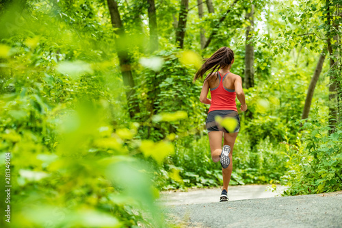 Foto Healthy active lifestyle woman runner jogging in forest path sport athlete training outdoor in green nature