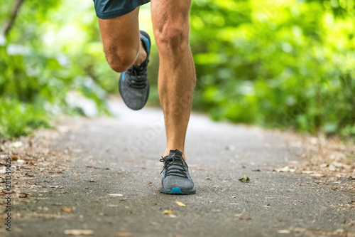 Leinwand Poster  Running man runner athlete workout jogging outdoors on city park path with running shoes closeup of feet and legs