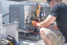 HVAC Technician Working On Controls Of Air Conditioner