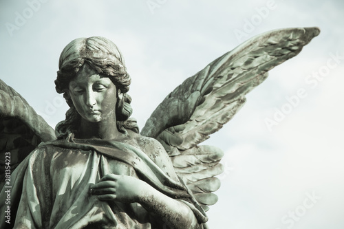 Fototapety, obrazy: Sad angel sculpture with open long wings across the frame desaturated against a bright white sky. The sad sculpture with eyes down and hand in front of chest.