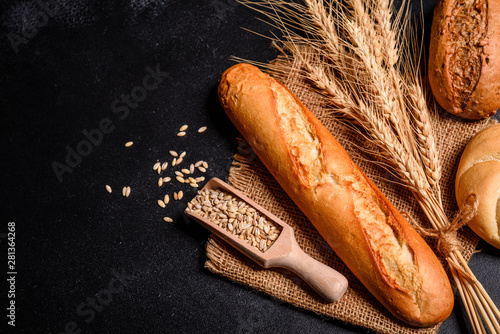 Photo sur Aluminium Boulangerie Fresh fragrant bread with grains and cones of wheat against a dark background. Assortment of baked bread on wooden table background. Fresh fragrant bread on the table