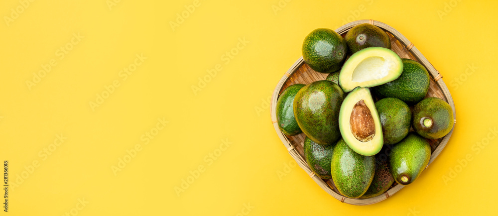 Fototapeta organic avocados half cut with seed and whole fruit in bamboo basket on yellow table background top view.Healthy super foods for diet.Fresh vegetable from farm.keto food ingredients.banner mock up.