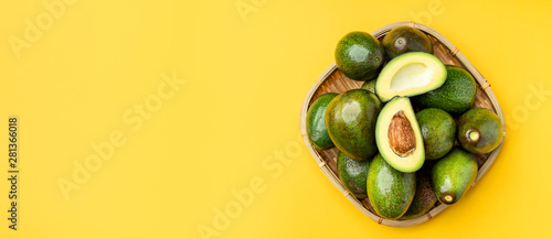 Fotografiet  organic avocados half cut with seed and whole fruit in bamboo basket on yellow table background top view