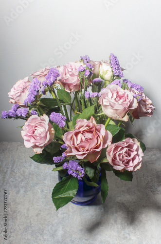 Valokuva  A bouquet of powdery pink roses on a gray background