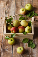 Ripe green and red apples in wooden box.
