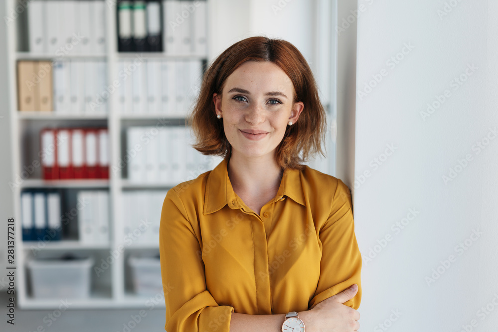 Fototapeta Self-assured relaxed young businesswoman
