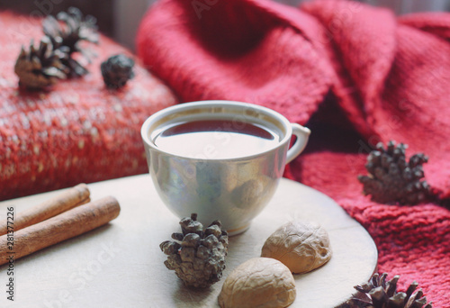 Foto op Canvas Chocolade Cozy picture, a сup of hot tea on a wooden board, fir cones, walnut shells, cinnamon sticks, red sweater and scarf