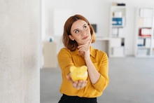 Thoughtful Businesswoman Holding A Piggy Bank