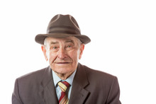 Portrait Of 90 Year Old Senior Man In Retro Hat Looking At Camera Isolated On White Background.