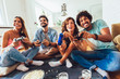 canvas print picture - Group of friends play video games together at home, having fun.