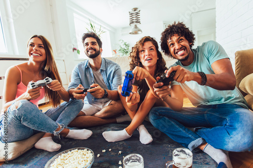 Obraz Group of friends play video games together at home, having fun. - fototapety do salonu
