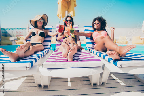 Obraz Nice attractive glamorous cheerful cheery slim thin fit girls lying on sunbed at modern fashionable spa resort hotel country club roof top having fun clinking glasses cold lemonade bachelorette - fototapety do salonu