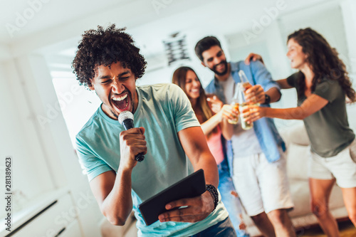 Group of friends playing karaoke at home. Concept about friendship, home entertainment and people - 281389623