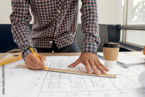 Crédence de cuisine en verre imprimé Kiev Close-up of young engineer in checked shirt using ruler and drawing the blueprint of new building or house with pencil at office