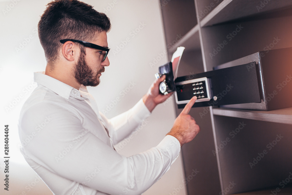 Fototapeta Men's hand opens a safe hidden in the wardrobe. Small home or hotel safe