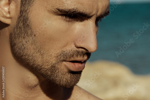 Fotografie, Obraz  Strong face male model on the nature background with rocks and water on the beac