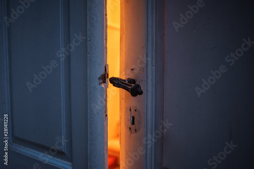 orange light from ajar old door.  intrigue disclosure concept Canvas Print