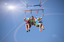 Two People Parasailing On Beach In Summer. Happy Couple Kissing Under Parachute In Air Above Surface Of The Sea