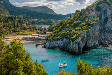 Beautiful Landscape With Sea–lagoon, Beach, Colorful Boats On Turquoise Water Surface, Mountains And Cliffs, Green Trees And Bushes, Blue Sky And Clouds. Corfu Island, Greece.